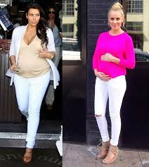 Two Women Wearing White Jeans Tops And Parka Coats They Are Pregnant