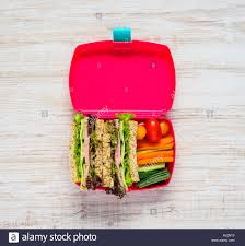 Top View Of Open Pink Lunch Box With Sandwich And Vegetables