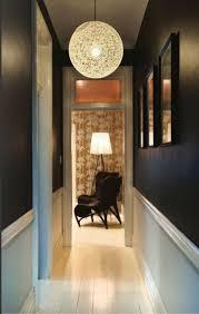 narrow hallway with black walls and hanging globe pendant lighting