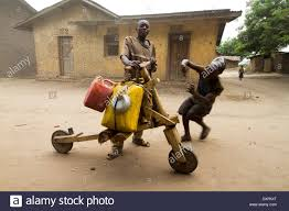 Villagers With Water Can Mounted On Chukudu Homemade Wooden Scooter In A Village Near Rutshuru North Kivu Congo DR Africa
