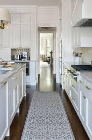Stunning White Kitchen Boasts A Gray Trellis Runner Placed Between Shaker Cabinets Adorning Brass Pulls