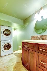 grünes badezimmer mit fliesen beige boden holzwaschbeckenschrank das badezimmer hat eine waschküche mit waschmaschine und trockner