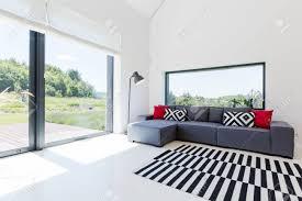 sehr helles wohnzimmer in einem modernen haus mit einem großen ecksofa und panoramafenster mit blick auf malerische nachbarschaft