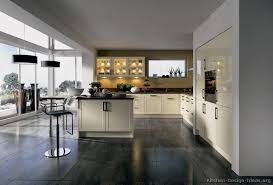 A Modern Kitchen With Cream Cabinets Gray Tile Floors And Wide View Of