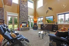 luxushaus offenen grundriss geräumiges wohnzimmer mit hoher decke backsteinsäulen und feuerstelle mit ledermöbeln eingerichtet
