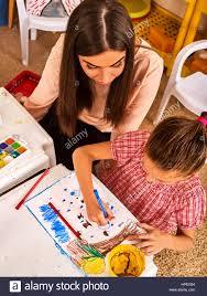Child Painting And Drawing In Kids Club Craft Lesson Primary School Kindergarten Teacher Help Small Student Kid Girl Coloring Picture On Table C