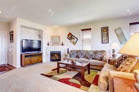 weiß wohnzimmer mit kamin und bunten teppich mit braunen sofas und couchtisch eingerichtet