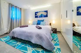 großes helles modernes schlafzimmer mit einem kingsize bett das in grün und blautönen mit kissen wandkunstmalerei teppich und einladenden