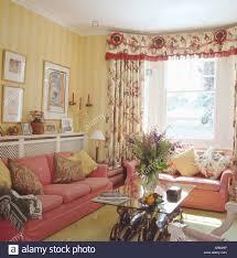 rosa sofas und gelb gestreifte tapete in wohn und esszimmer