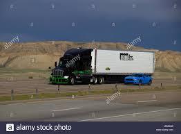 A Black Peterbilt Semi-Truck Pulling A White