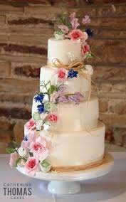 Gorgeous 4 Tier Rustic Styled Wedding Cake Decorated With A Cascade Of Hand Made Sugar Ranunculus Flowers Roses Sweet Pea Sprigs And Cornflowers