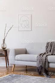 stilvolles scandi interieur des wohnraums mit design grauem sofa und retrokleinem tisch wohnzimmer mit designaccessoires und verspotteten plakatrahmen