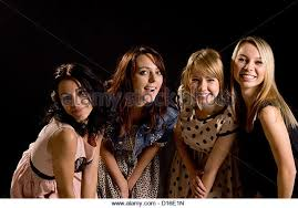 Four Laughing Teenage Girls In Stylish Outfits Having Fun Leaning Forwards Together With Mischievous Smiles On