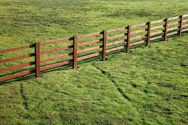 Wooden Ranch Style Fence On Grass Field