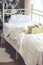 Wrapped Presents On A Bed Near Decorated Christmas Tree In Hotel