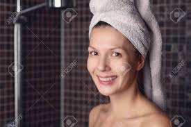 glückliche nackt attraktive frau mit ihr nasses haar in ein handtuch standing in ihrem badezimmer lächelt in die kamera in einer gesundheit schönheit