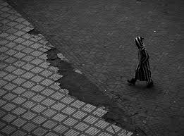 An Urban Person Walking On A Sidewalk In Black And White Marrakesh