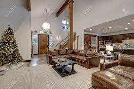 gewölbedecke wohnzimmer mit holzbalken über braune ledersofas akzentuiert offener grundriss nordwesten usa