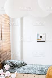 poster zum thema weiße wand und blumen in einfache schlafzimmer innenraum mit gemusterten kissen im bett echtes foto stockfoto und mehr bilder