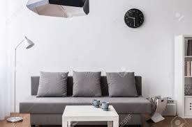 modern minimalistischen wohnzimmer in grau ausgestattet und weiß mit designerleuchten
