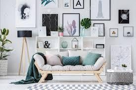 beige sofa mit grünen kissen neben hängenden hocker gegen eine wand mit poster in flachen interieur mit blatt in vase