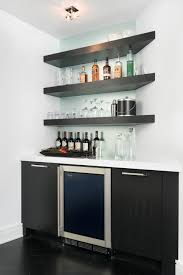 This modern wet bar features floating corner shelves and a frosted