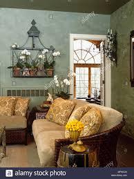 holz sofa mit gelben kissen in grün landhausstil wohnzimmer