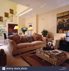 beige sofa und gemusterten gepolsterte ottoman hocker im