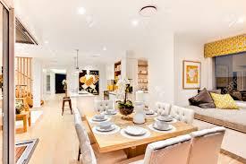 moderne speise mit holztisch im wohnzimmer in der nähe der ruhebereich auf holztreppe und flur mit kissen und polster matratze neben neben der küche