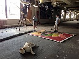 Painter Chris Toepher inside the Old Main Post fice building with the Blackhawks mural he installed