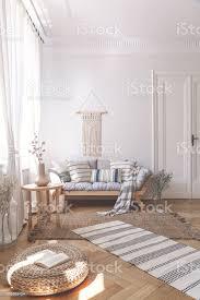 sonnenstrahlen auf eine weide osmanischen und fischgräten stock ein beige wohnzimmer interieur mit einem hölzernen sofa und kissen stockfoto und mehr