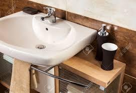 detail eines modernen badezimmer mit waschbecken und zubehör badezimmerschrank und braunen fliesen im bad