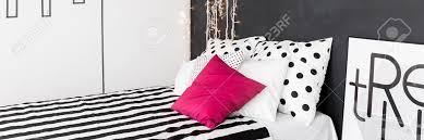 schwarz weiß wohn interieur mit bequemen bett muster bettwäsche und rosa kissen