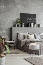 farben schlafzimmer innere erde mit ein großes bett ein sessel ein hocker in einem modernen gemütlichen hotel schwarzen gemälde auf einer