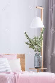 blumen in einer vase am rosa bett im gemütlichen schlafzimmer