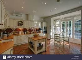 Butchers Block In Country Style Spanish Kitchen With Terracotta Tiled Floor And Glass Dining Table White Chairs