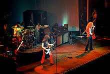 A Colour Photograph Of The Four Members Led Zeppelin Performing Onstage With Some Other