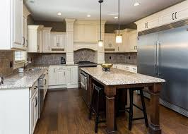 Kitchen With Raised Panel Antique White Cabinets Dark Wood Floors And Rustic Island