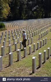 Woman Walking Through Headstones In National Veterans Cemetery