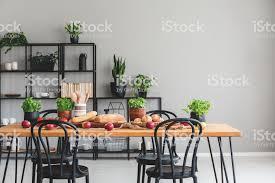 schwarzen stühlen am holztisch mit äpfeln und basilikum in grau esszimmer interieur mit pflanzen echtes foto stockfoto und mehr bilder apfel