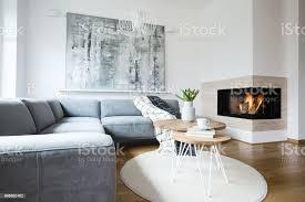 graue ecke sofa mit decken stehen in weißer nordic wohnzimmer interieur mit frischen tulpen bücher und teetasse auf haarnadel tabellen abstrakte