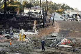 EMERGENCY PERSONNEL LOOK OVER THE CRATER FROM A GAS LINE EXPLOSION SEPTEMBER 10 2010 IN