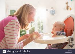 Mother Feeding Baby Girl In High Chair Stock Photo: 66805788 ...