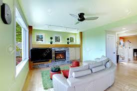 grüne wohnzimmer mit fernseher schwarz und beige sofa mit kamin