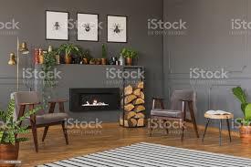 echtes foto zwei graue sessel stehen vor einem regal mit kamin und pflanzen le und eine wand mit poster in vintage wohnzimmer interieur