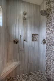 master shower with seat and shelf pebble tile floor and accent