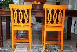 Wooden Table Orange Painted Chairs On Patio