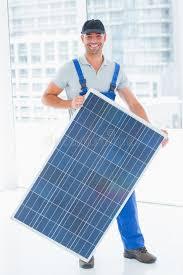 le bureau solaire travailleur manuel tenant le panneau solaire dans le bureau
