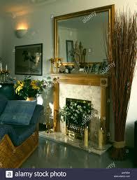 vergoldeter spiegel über dem kamin im wohnzimmer mit