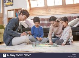 Harmonious Family Playing A Board Game Together In Living Room